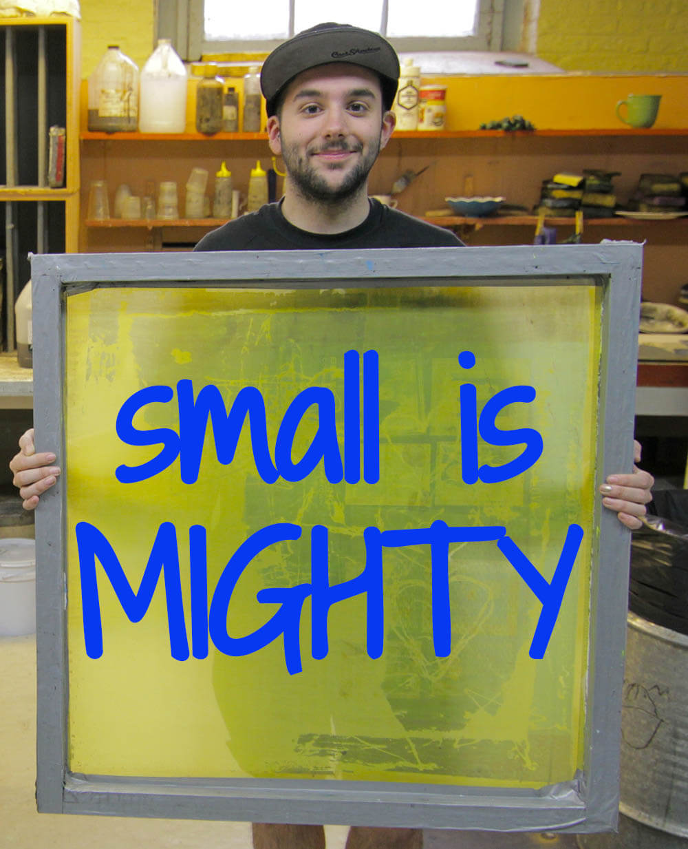 student holding sign which reads small is mighty